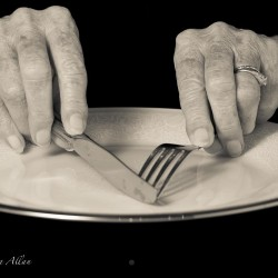 Mother's eating with knife and fork hands with Parkinson's Disease