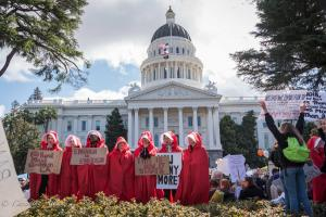 Capitol building with group of handmaidens in red robes with signs March for Our Lives rally protest guns sacramento california 3242018 DSC 9076