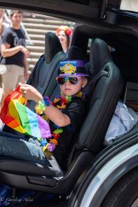 Child in tesla rainbow lei gay pride parade lgbtq sacramento california allan