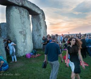 Lady with pink earrings in hair stonehenge summer solstice  england allan