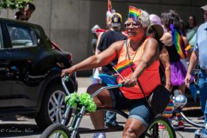 Older black african american woman on bike rainbow flag gay pride parade sacramento