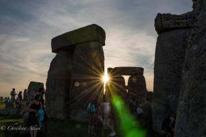 Sunburst and green diffraction silhouette stones stonehenge summer solstice  england allan
